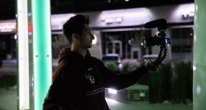 Vlogger holding camera - Blogging vs Vlogging - which is better