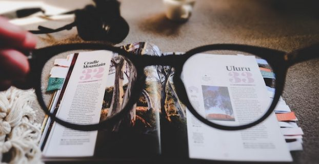 looking through glasses reading a magazine