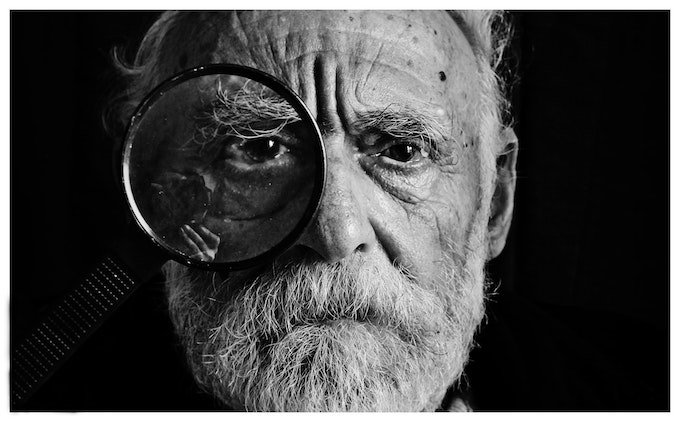 old man with magnifiying glass - observe people for writer's block